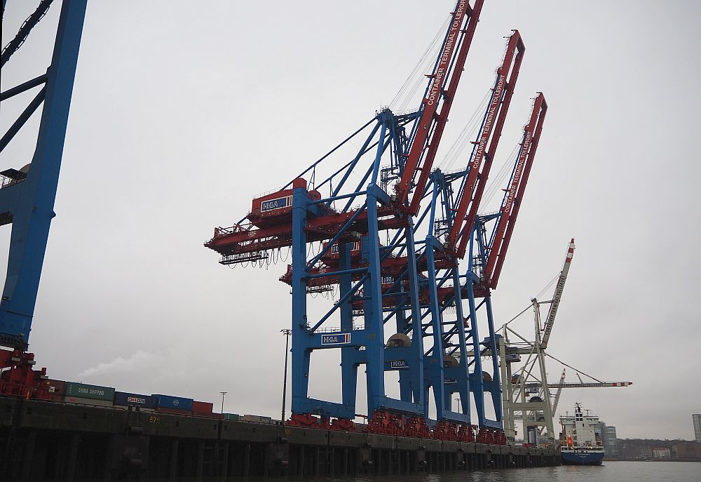 a row of blue and red cranes line a dock in Hamburg