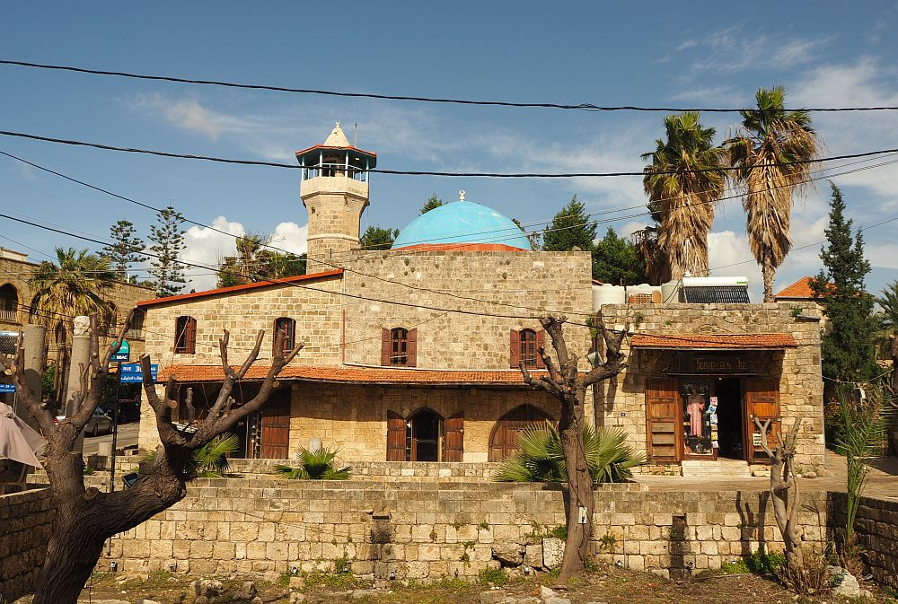 The mosque is made of stone blocks and has a stone minaret and a blue dome.