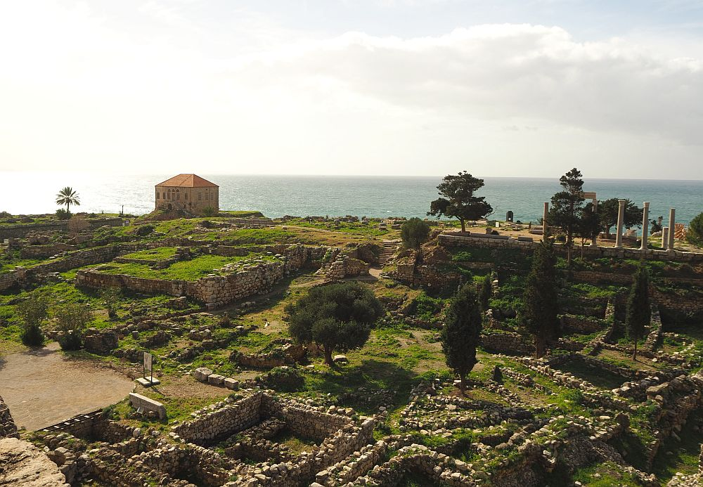low stone walls, roman columns and the sea beyond.