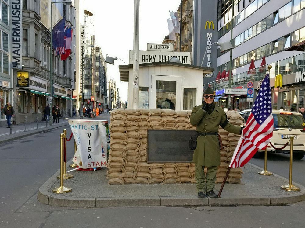 Checkpoint Charlie, the most famous Cold War site in Berlin, is a small hut. In front is a low wall of sandbags, and in front of that, a man dressed as a soldier, holding an American flag. On both sides, a busy city street in Berlin.