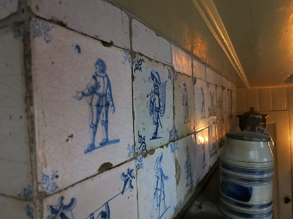 The tiles are a bit chipped around the edges and show simple human figures in blue on a white background.