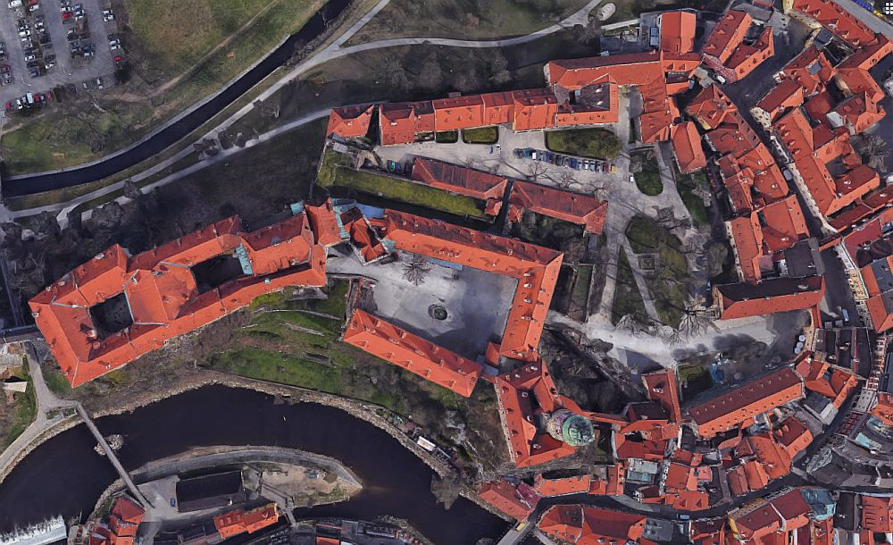 view of the castle from above, which looks just like a collection of buildings with orange roofs.