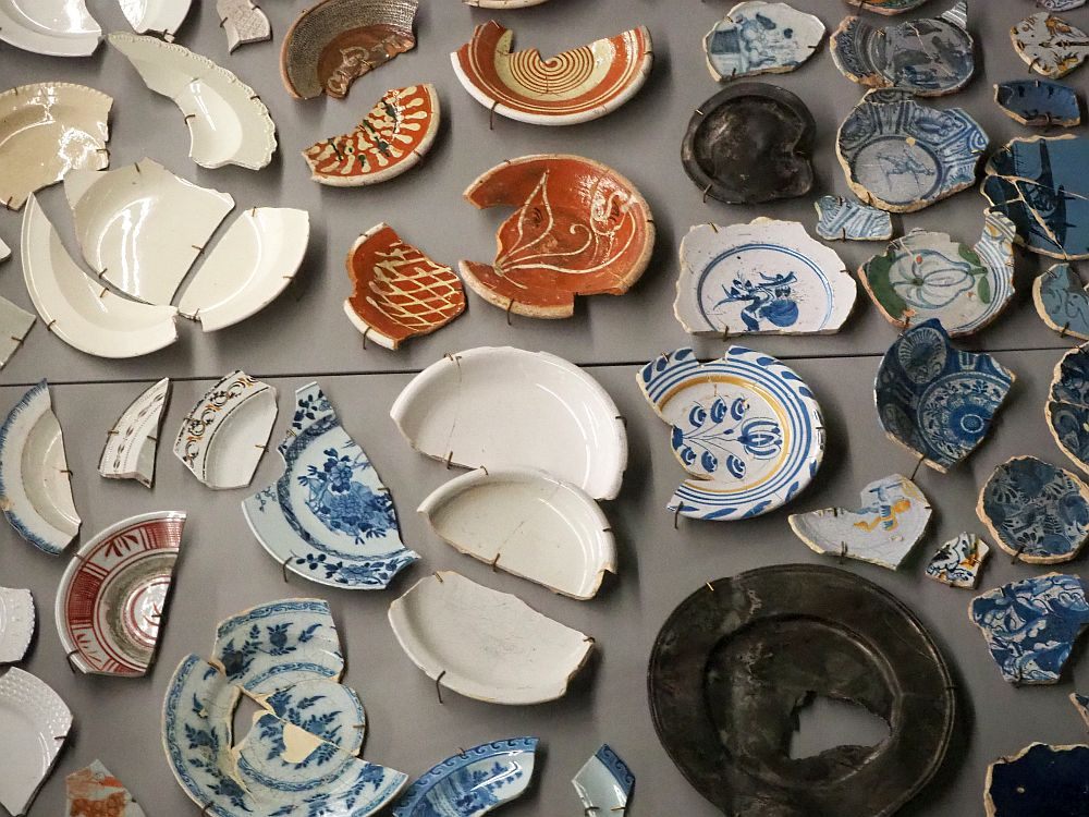 The dishes pictured are all broken and pieced together, though most also still have portions missing. Several are blue and white Delft ware, while some are plain white or earthy brown.