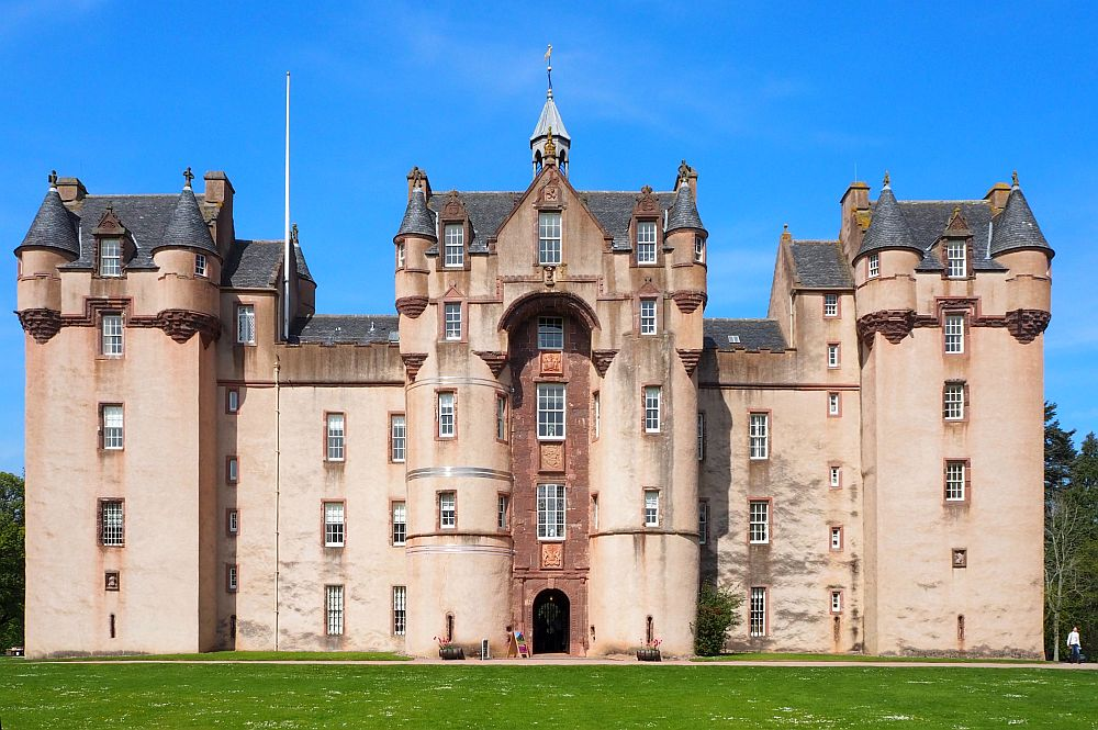 A massive, imposing castle with a huge archway over the front door and massive towers on both sides.