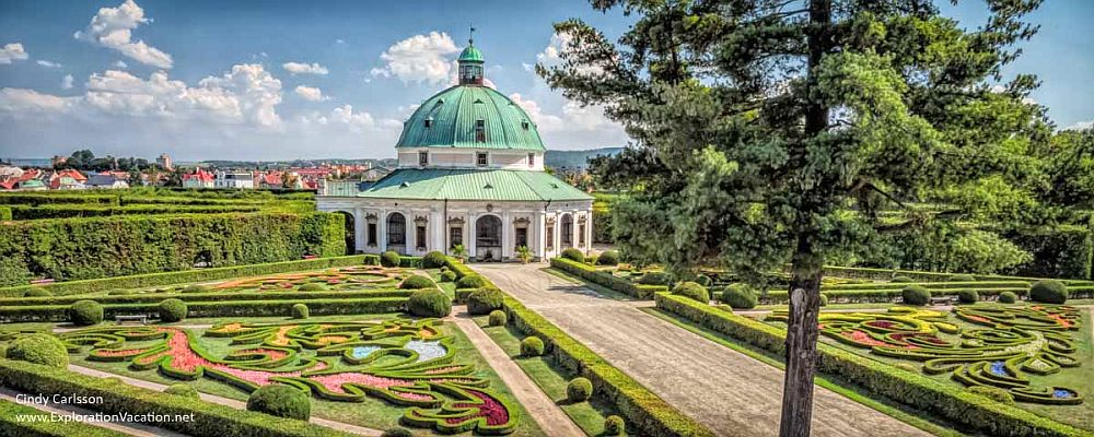 plantings in the foreground are ornately-trimmed in baroque style geometric patterns. In the background, a green-domed, round folly, called the Rotunda.