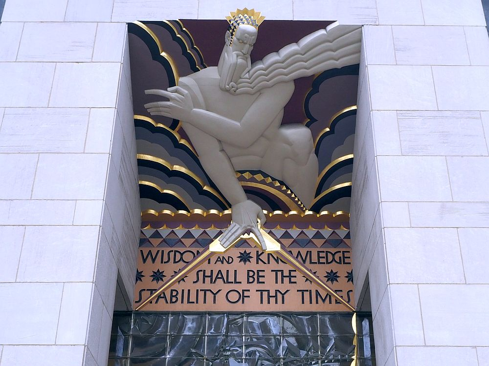 """The figure of a god leans over the entrance. Underneath it is the text """"Wisdom and knowledge shall be the stability of thy times."""""""