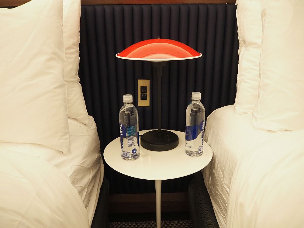 The table is small white pedestal table. On it stands two bottles of water and a lamp with a red domed top.