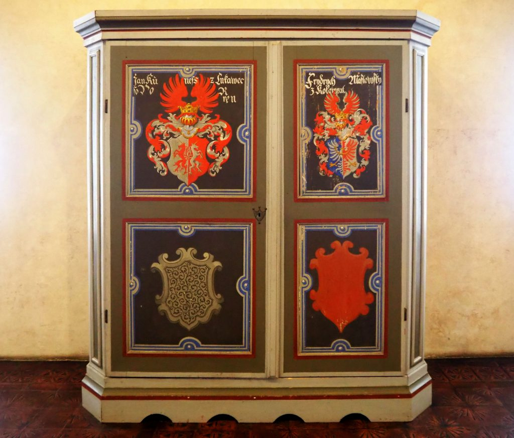 The cabinet is painted in bright colors, with four shields depicted: coats of arms, perhaps. The two top ones seem complete while the two lower ones are only outlines.