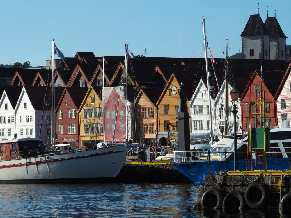 A row of houses all adjoining each other, painted in a range of colors. In front of them, several boats are moored.