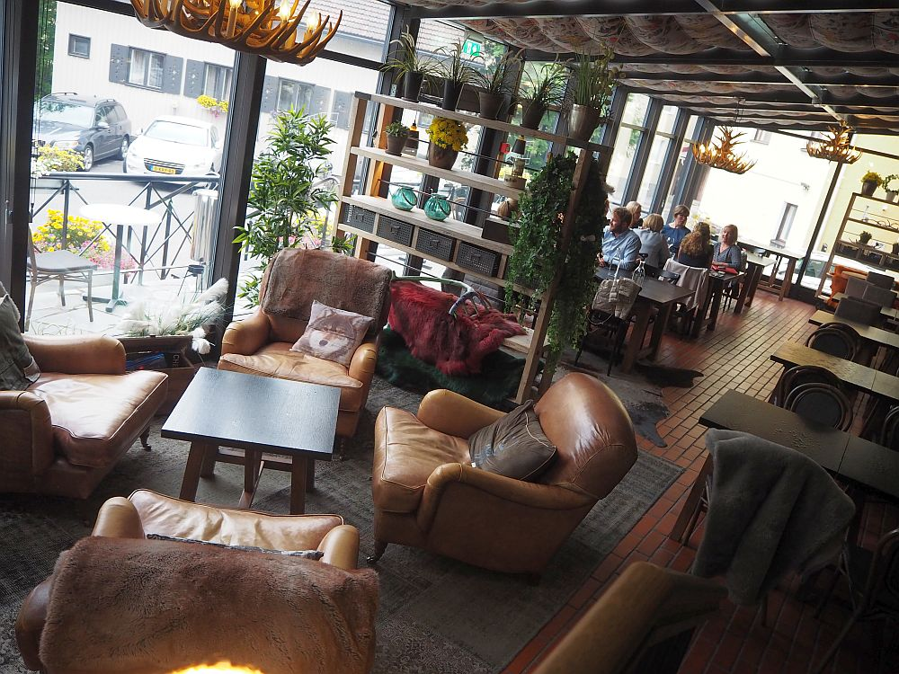 In the foreground, a cluster of soft brown armchairs with cushions. In the background, tables with people sitting at them. A brown shelving unit divides the two spaces, and big windows let in lots of light.