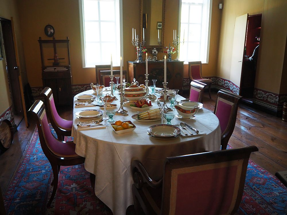 The Menkemaborg dining room has a relatively modest looking table, set for six people, with a white tablecloth, silver candlesticks, and what looks like fine china and silverware. The chairs are simple yet elegant, with gently curved backs and upholstery in dark reddish-purple. The room's floor is wood boards, but the table and chairs sit on an oriental carpet.