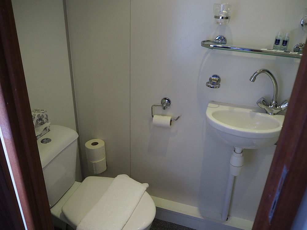 The toilet in our Boat Bike tours cabin is visible on the left and the sink is on the wall opposite the camera.