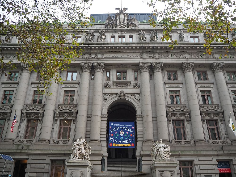 """A very grand front to the building: granite, with corinthian columns and ornate sculptures on either side of the entrance stairway. A banner hangs above the entranceway reading """"Day of the Dead. Dia de los muertos"""""""