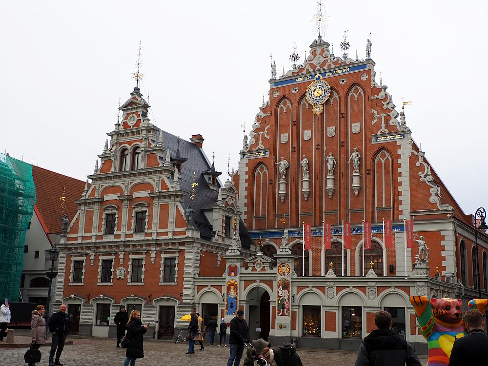 This building looks like two buildings: each with a triangular facade. Both are red brick with white detailing. The building on the right has ornate decorative features between and above all the windows (it's about 4 stories tall). The facade on the right is far more ornate, with a very decorative roof line and a row of human statues across the middle front. The ground floor has arched windows and an arched entryway with colorfully painted figures on either side and statues above it and on the corners of the building.