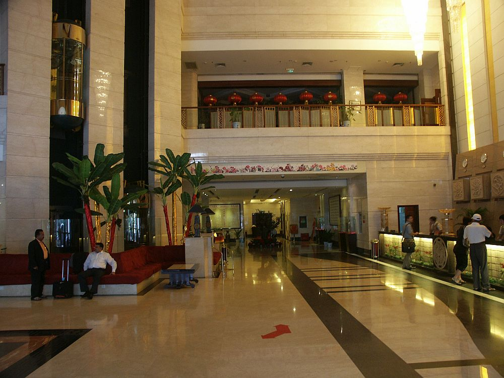 The lobby is several stories tall with a big empty space in the middle with a shiny white floor. On the right are the check-in desks. On the left, a few people sit on a bench. Behind them is a cluster of small trees and behind them, a glass elevater is stopped on the floor above. In the back of the shot a balcony is visible one floor up.
