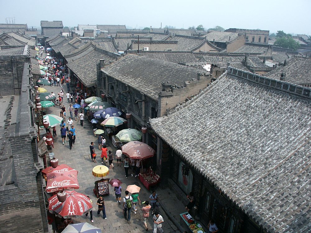 a view from above of a street lined with simple brown brick building, with slightly curving roofs in the Chinese traditional style. More such houses can be seen in the background. ON the street that stretches into the distance, umbrellas cover street stalls on both sides and people walk down the middle between them.