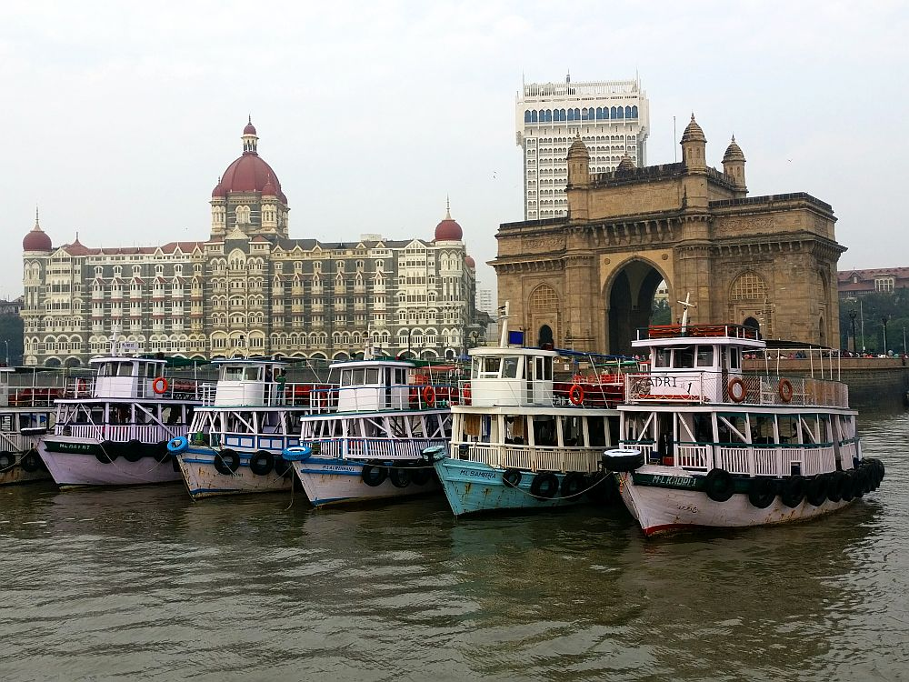 In the foreground is a row of small boats, each with a railing around an open deck. Behind them is, to the left, an elegant white building of perhaps 7 stories with a round red-roofed cupola in the center and smaller domes on each corner. Some of the many windows are arched and some are not. On the right is a brown stone structure with a high archway in the center and two smaller archways on either side.