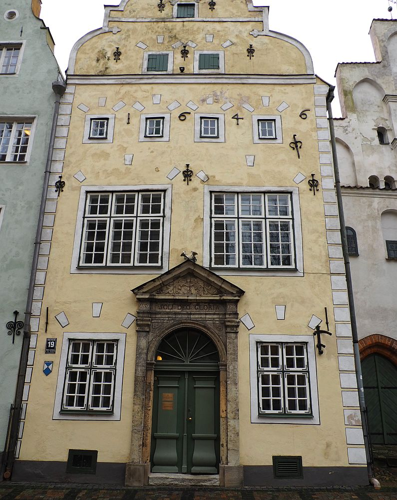 """The picture is mostly filled with the middle house. It is pale yellow with an arched doorway with a triangular pediment above it. The windows of the building (3-4 stories) are multi-paned and edged in white and black. Letters on the 3rd story read """"1646."""""""