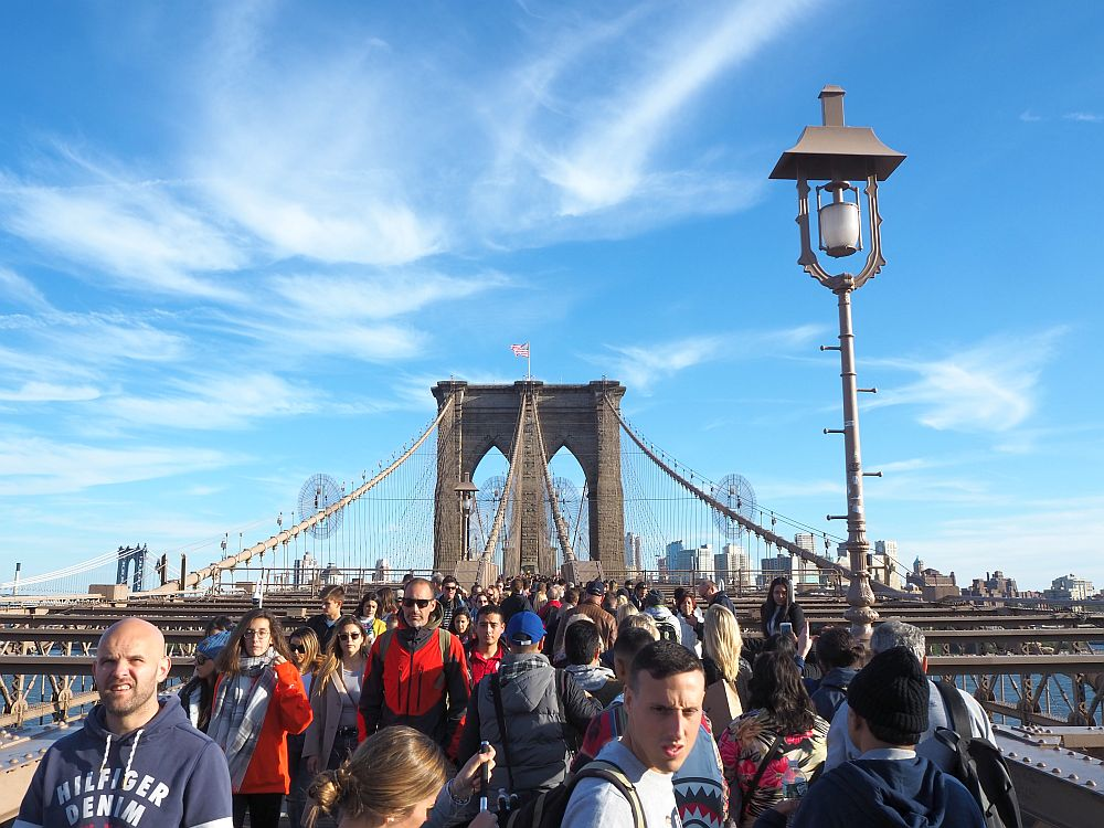 This photo shows the crowds walking across the Brooklyn Bridge when I was there. The walking path is wider here, but even fuller with people walking in both directions and no bikes visible. In the background is one of the support towers, the cables sloping up to it, and a few tall buildings in brooklyn can be seen in the far distance.