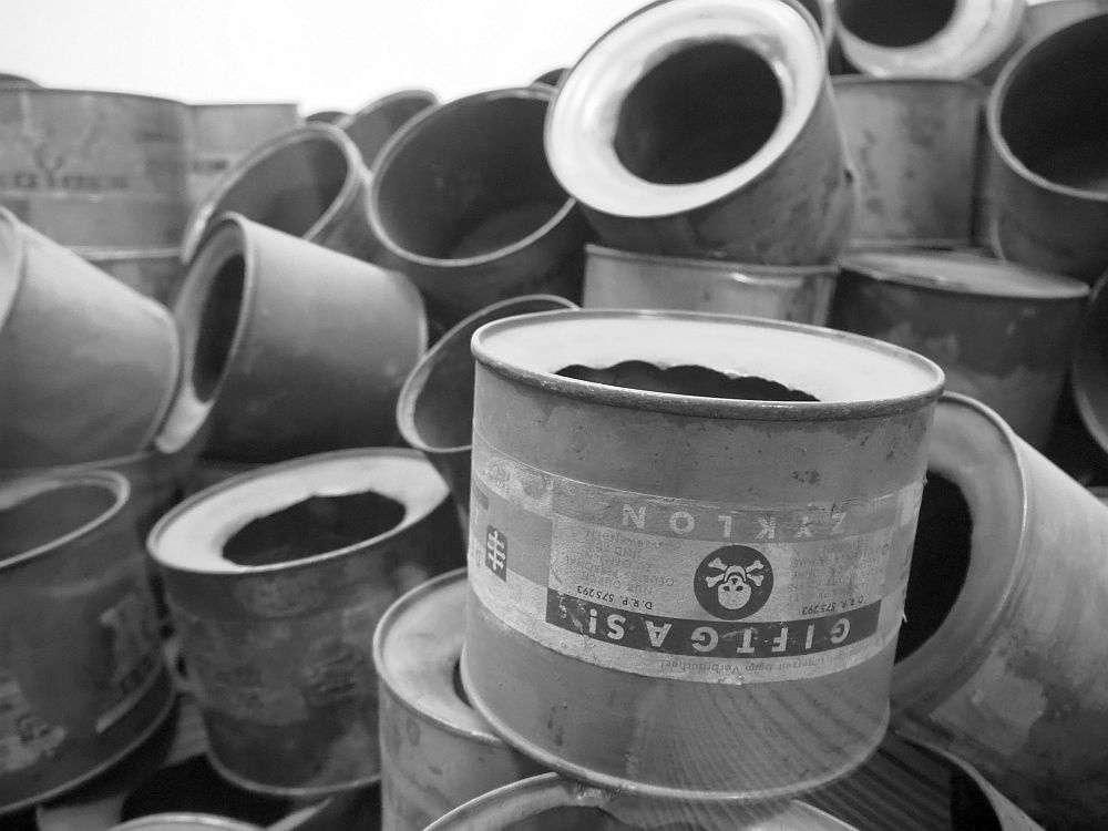 """Black and white picture of a pile of empty cans of Zyklon B. Each is round, and one end has a large hole in the center. The nearest one is legible: """"Giftgas! Zyklon"""" with a skull and crossbones symbol."""
