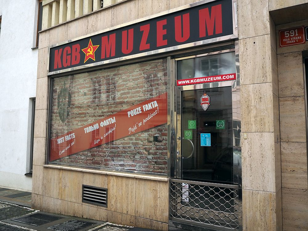 """The store front reads """"KGB Muzeum"""" with a red star with a hammer and sickle inside it. The store window appears to be bricked up."""