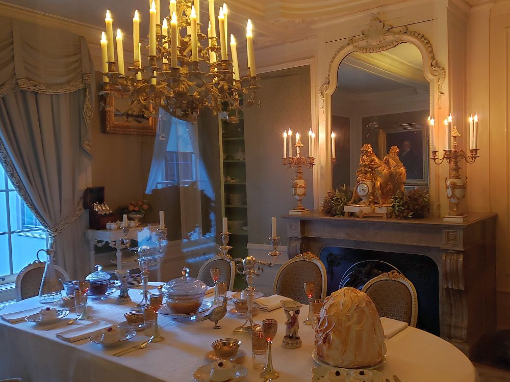 The table is set with a white tablecloth and napkin, silverware and fine china. The chandelier is smaller and simpler than in the ballroom. The mantelpiece is also simpler, with a baroque-looking gold clock sitting on it, along with two candlesticks, each holding 5-6 candles. A large mirror backs the clock.
