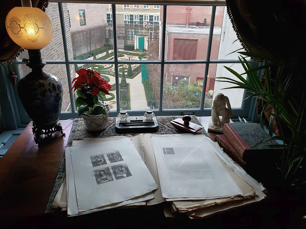 On the dest is a small oil lamp, a book open, a poinsettia plant, a couple of closed books and other small odds and ends. The light comes through the window, which looks out on the garden, all in neat, symmetrical, carefully trimmed low hedges.