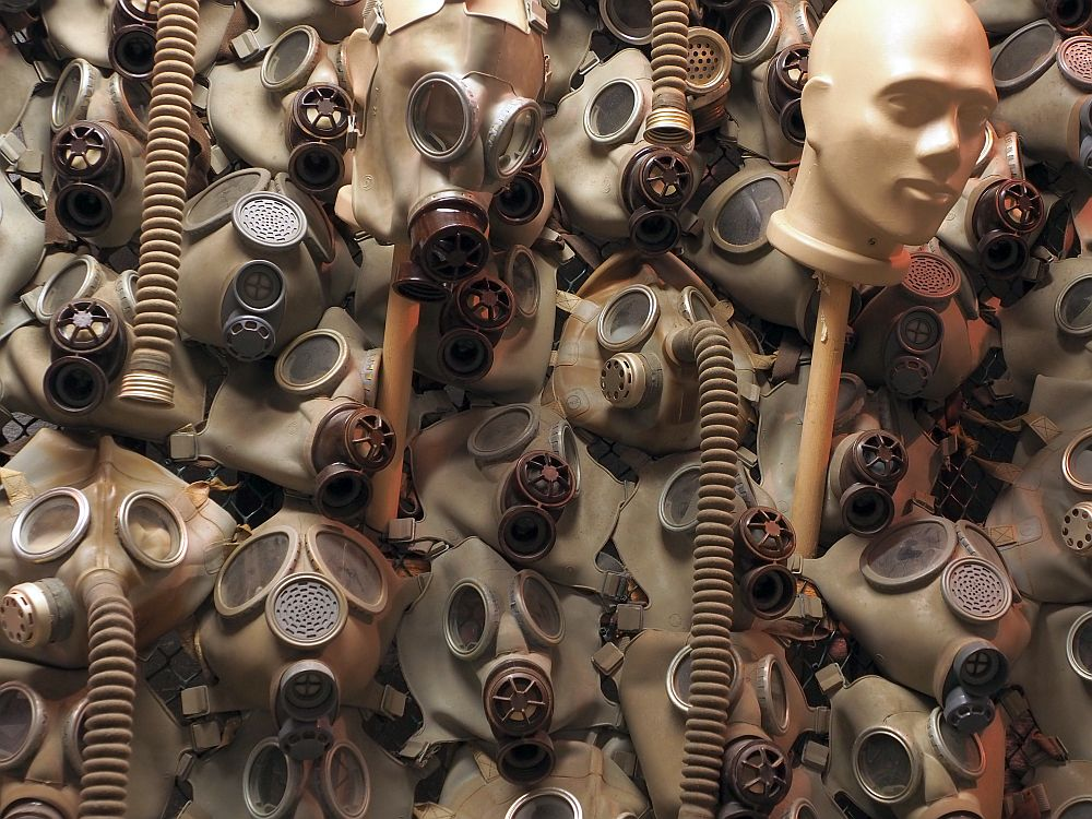 The gas masks are mounted on the wall so that none of the wall is visible: it's just a hodgepodge of gas masks and hoses and one mannequin head.