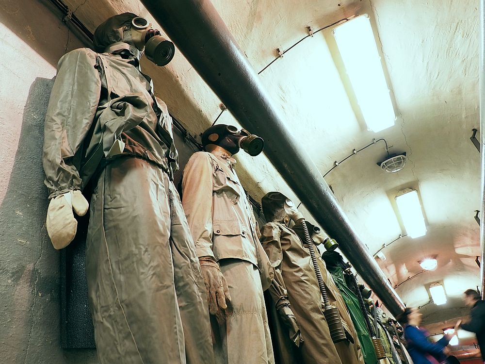Taken from floor level, looking at a row of mannequins, each dressed in what looks like rain jackets and pants and wearing a gas mask and mittens.