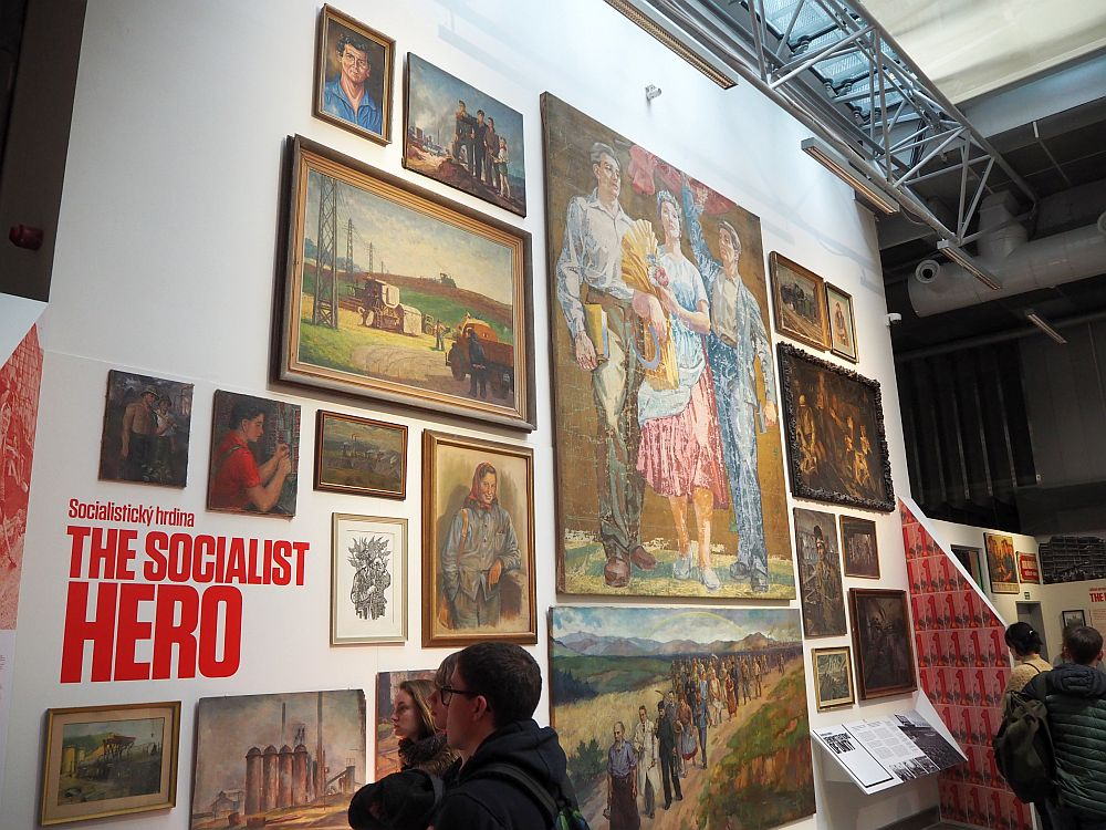 """The wall is about two stories high and is covered with artworks, mostly showing things like proud peasants and workers in idealized country settings. A few people at the bottom of the photo look at them. The title painted on the wall reads """"The Socialist Hero"""""""