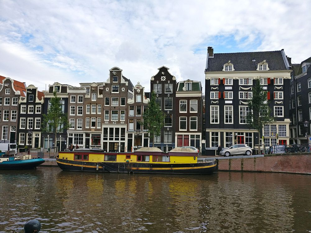 A row of 10 canal houses with a yellow house boat moored in front of them. The houses have a range of different styles of gables, but all are red or brown brick and have many windows, with more windows on the ground floor. The Canal House Museum Amsterdam gives information about how such houses were built.