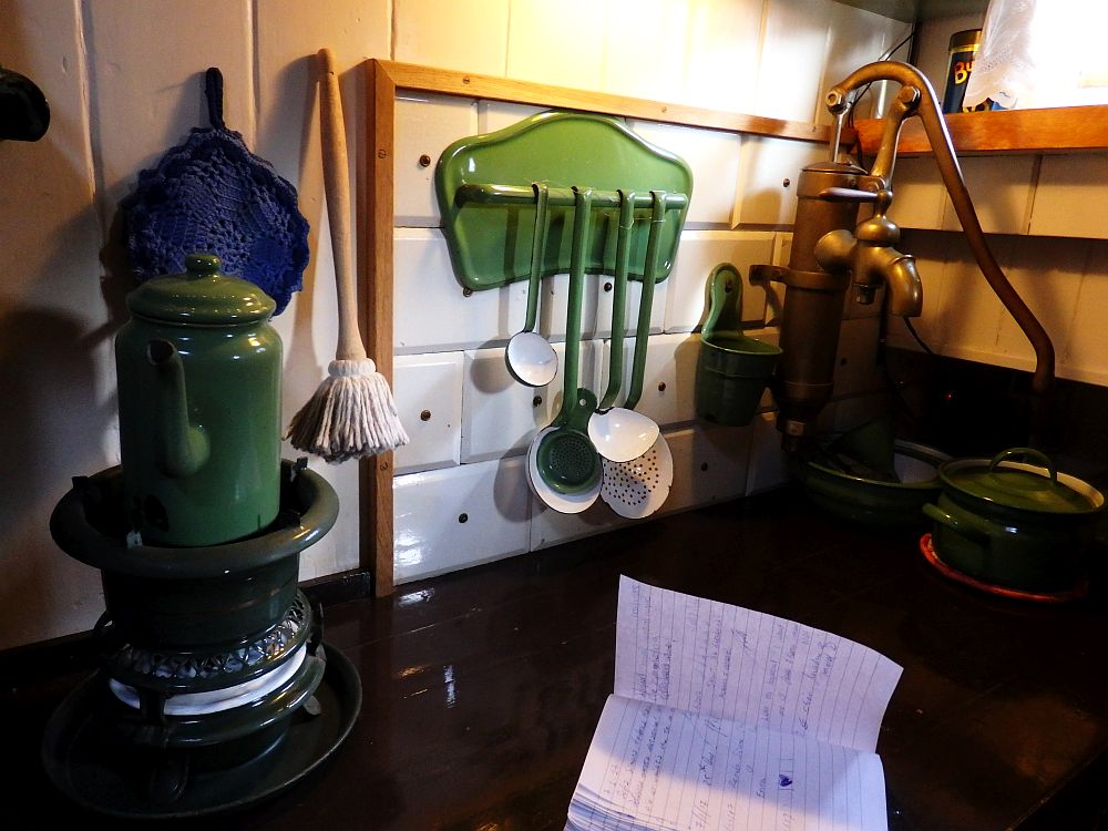 A round stove on the left has a green coffepot on it. A green metal rack has four utensils (ladles) hanging from it. In the corner is a waterpump: the kind you have to pump a handle up and down to get the water up.