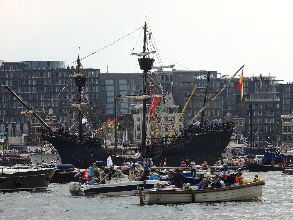 """Another general view. In the background, a row of modern apartment buildings. Moorred on the other side: another ship that looks like a pirate ship: black with a high bow and high stern, on which people are standing. It has two masts, each with a """"crow's nest"""" on the top. In front of that, on the river, lots of small motorboats pass, crowded with passengers."""