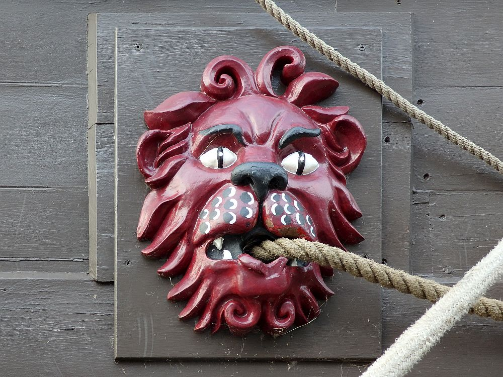 Closeup of a wooden carving, painted red, of a lion's head. It has a hole in its mouth for a rope to go through.