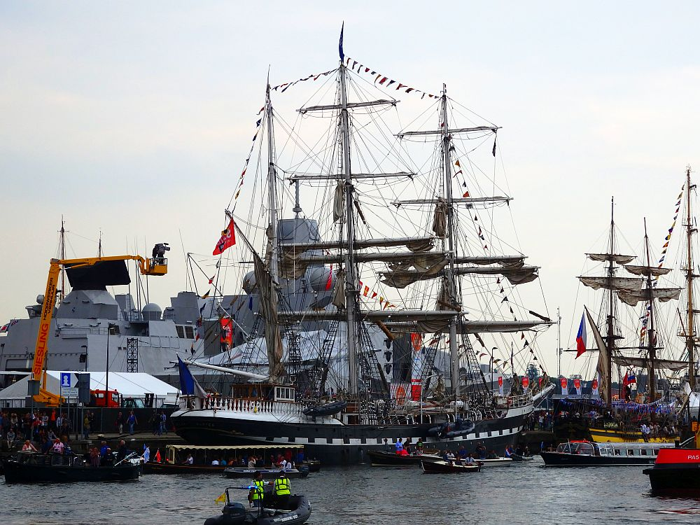 A tall ship with three masts, with small decorative flags strung along the top of the three masts and conneting to the bow and stern of the ship. Behind it is what looks like a military ship, modern and angular and painted grey.