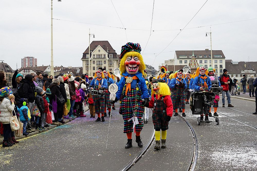 A parade coming toward the camera down a street. People watching on either side. A person with a huge smiling clownish mask, yellow hair, blue jacket and colorful plaid pants, holds hands with a smaller person, also wearing a clownish mask. Behind them, a marching band in similar clothes, but wearing clownish makeup rather than masks.