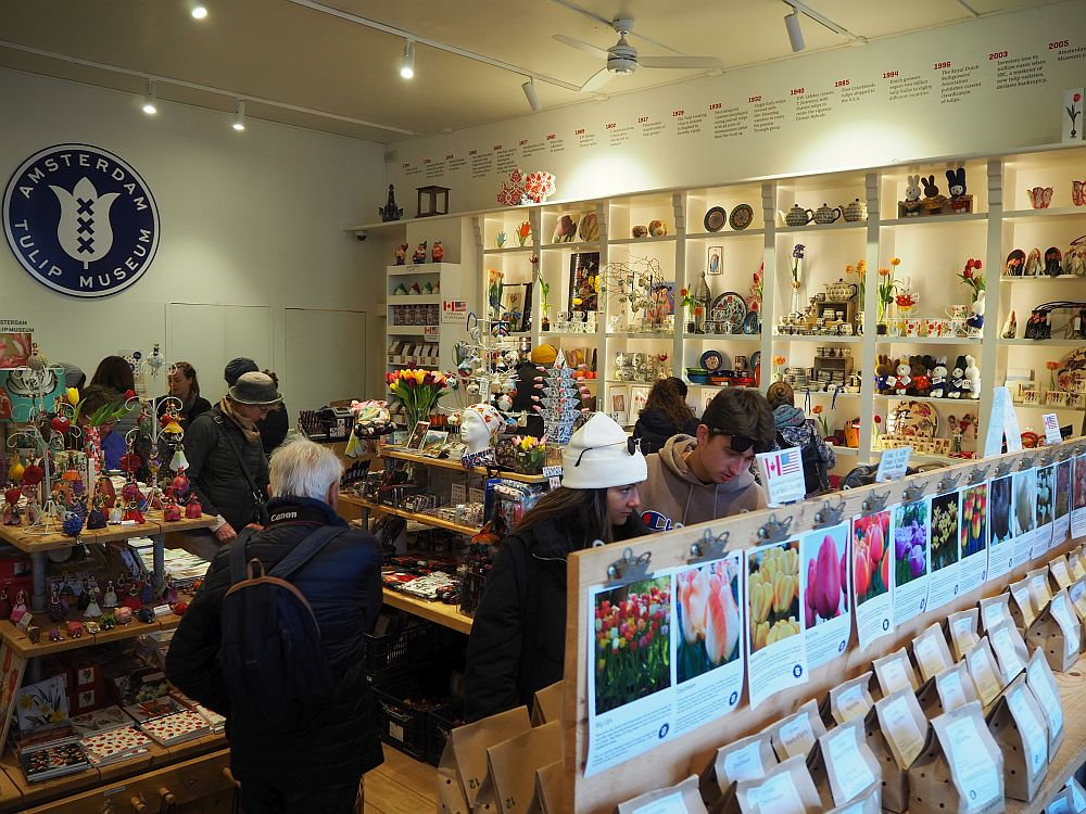 The shop in the Amsterdam Tulip Museum, seen from slightly above, filled with shelves and tables and lots of people among them. Bags of tulips are visible in the foreground and lots of brightly-colored objects cover the shelves and tables.