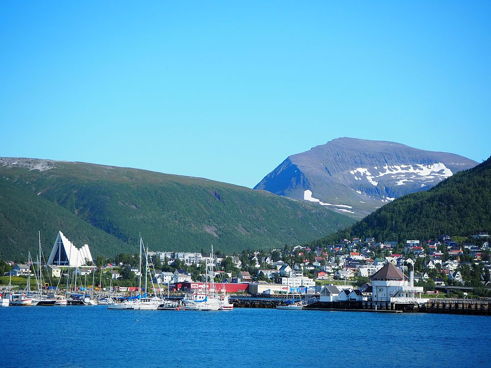 In the foreground, calm blue water. The buildings in the middle ground are mostly quite low-rise, clustered between two green-covered mountains left and right. In the background, another higher mountain, this one partly green but also with remnants of snow visible. Blue sky above.