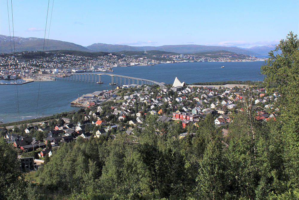 The nearer part of the city is a cluster of low buildings, with the Tromso Cathedral standing out as a bigger white building. The body of water is crossed by a long bridge, and beyond the rest of the city sprawls along the water, also low-rise. Beyond that: mountains.