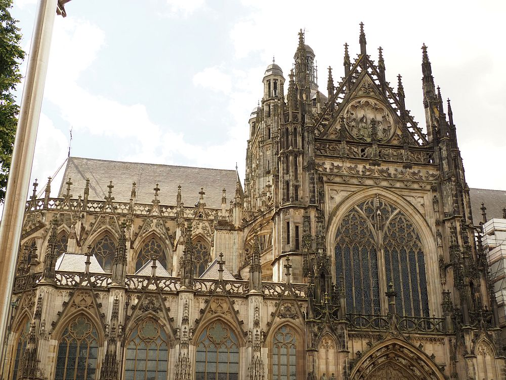 A gothic building: gothic arches with decorative crosses above them, a taller tower section with huge gothic arches and lots of turrets.