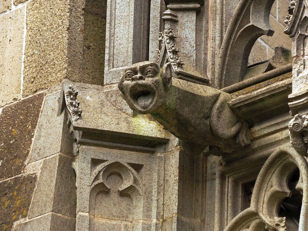 The gargoyle has a human face but an animals body and pointed ears. A devil? Its mouth is wide open.