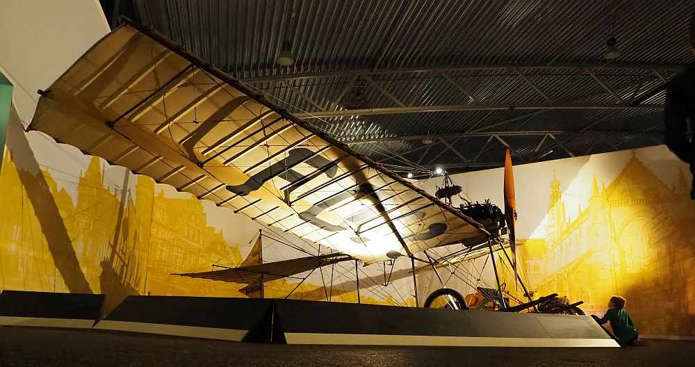 A very fragile-looking plain. Only the near wing is visible. It has a rod on the forward edge and ribs extending straight back from that. Canvas or some other material covers the ribbing. It has a single propeller on the front and a skeletal body. It resembles a dragonfly more than anything else.