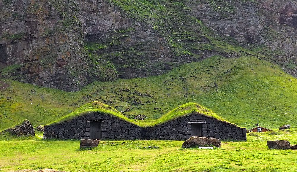 Seen from the front, each of the two parts has a peaked roof covered in grass. The center of each partk has a single doorway and no windows. The fronts are stone. Behind it is a steep cliff.