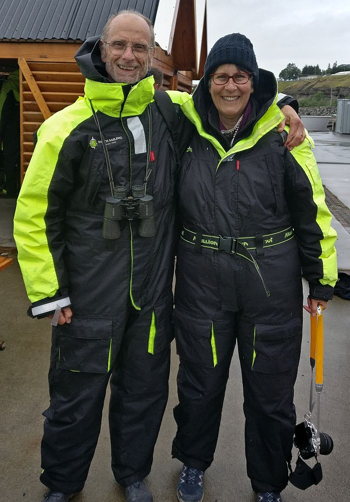 Albert and I pose facing the camera, arms around each other's shoulders. Both wearing a one-piece coverall, black, but with bright yellow along the tops of the sleeves and around the collar. I have a camera dangling from my hand and a warm cap on my head. Albert has a pair of binoculars hanging from his neck.