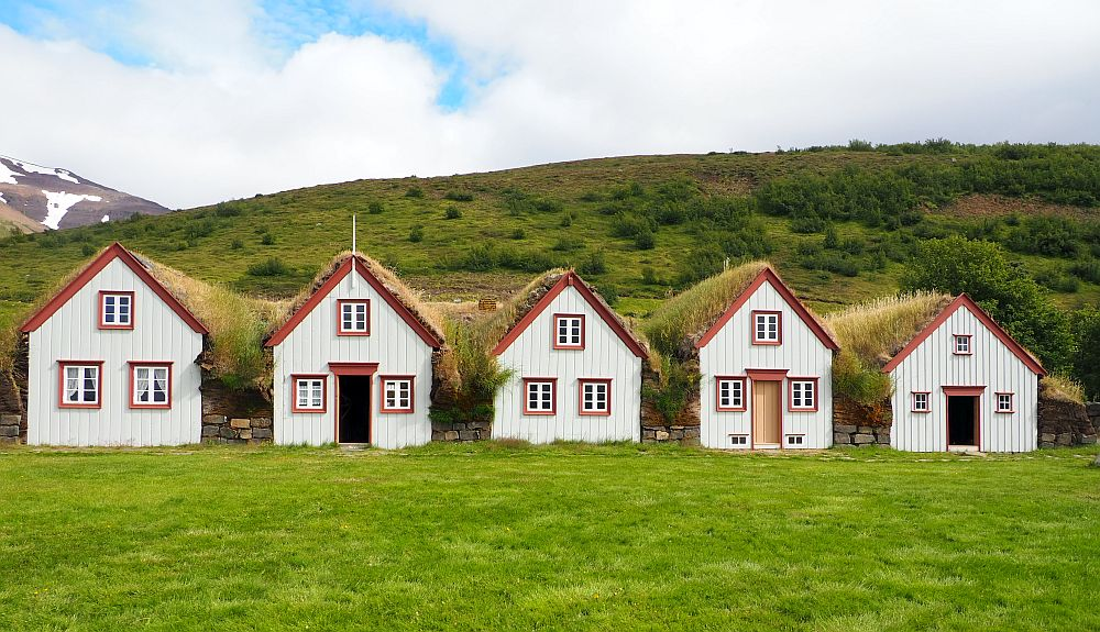 The turf farmhouse looks like a row of separate small houses, but they're actually attached inside. The five fronts here are all painted off-white with reddish-brown trim. Three of the five have a central door with a window on each side of it. The other two fronts just have two windows on the ground floor. Each front has an upper floor, each of which has a single window in the center. The roofs all have grass growing on them and the space between the fronts is all filled with turf blocks.