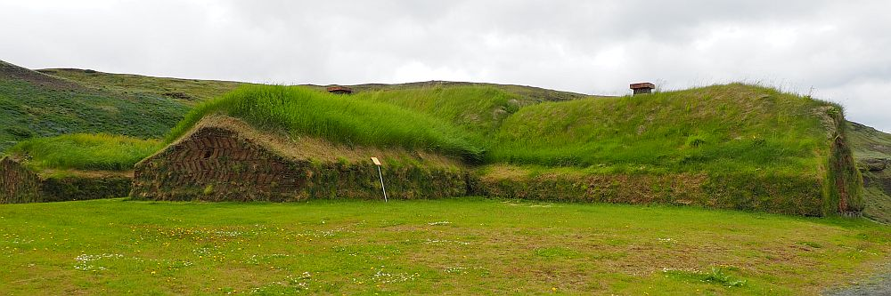 The house is low to the ground. Only the bottom of the walls is brown; the rest is all green with grass, as is the land in front of it. The photo shows two wings of the house, each long and with a simple peaked roof and no windows.