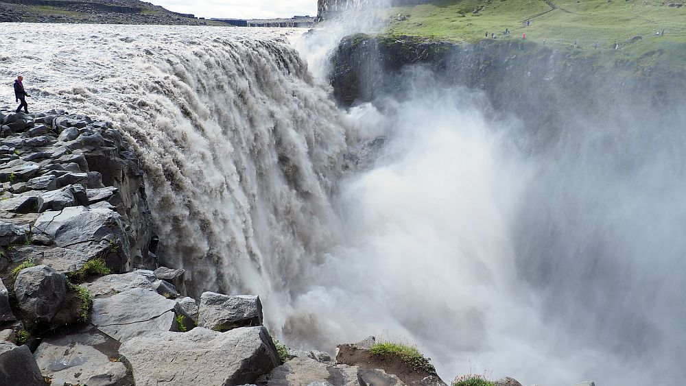 Seen from the level of where the water falls off its cliff shelf, the sheer quantity of water if visible and a lot of spray obscures how far it falls. A person stands right next to the waterfall at the left.