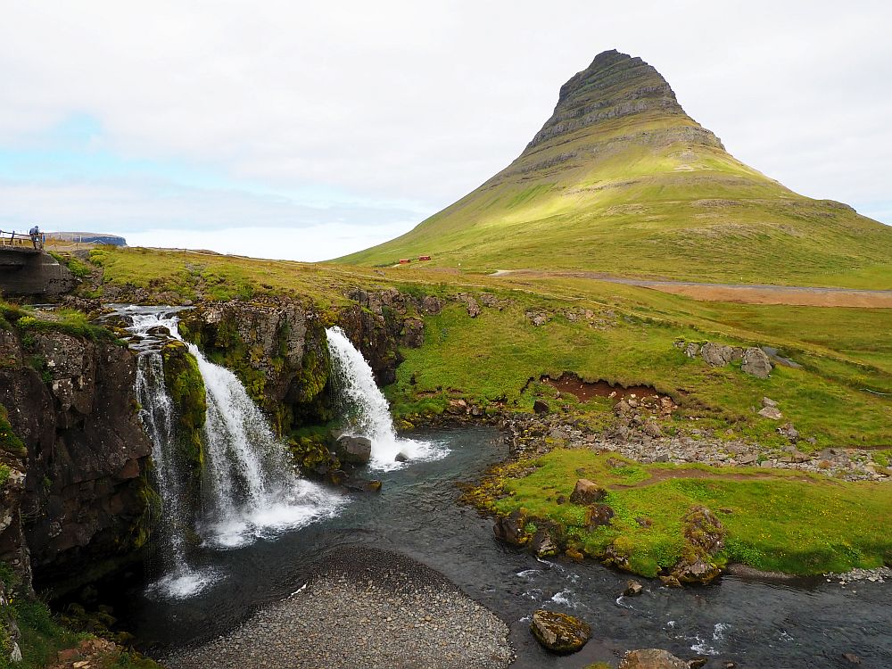 The waterfall descends at the left, split into several sections. Behind and to the right is a conical mountain.