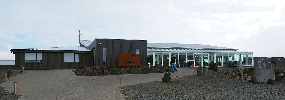 A long low building, brown with a light roof. the left-hand end has just a couple of windows. The right half has a glass wall and tables and chairs are visible inside.