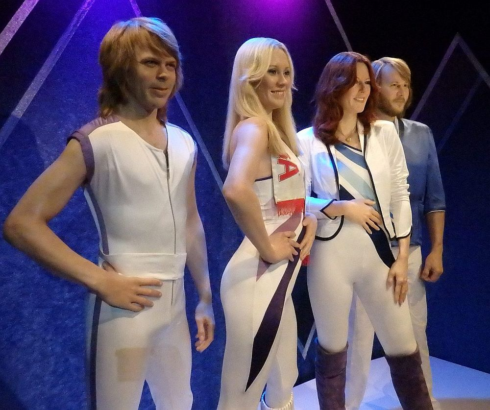 L-F: Bjorn Ulvaeus, Agnetha Faltskog, Frida Lyngstad and Benny Anderson. They're all wearing mostly white spandex jumpsuits. Benny has a light blue jacket over his. The wax figures in the ABBA Museum Stockholm look extremely lifelike.